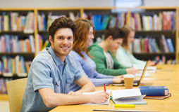 Happy student boy with books writing in library Stock Photo