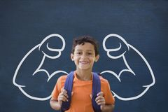 Happy student boy with fists graphic standing against blue blackboard Stock Photography