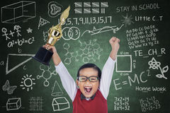 Happy student boy hold trophy in class. Happy student boy shouting while holding a trophy in classroom Royalty Free Stock Image