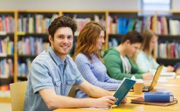 Happy student boy reading books in library Royalty Free Stock Images
