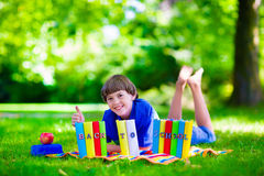 Happy student boy relaxing in school yard reading books Stock Photo