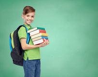 Happy student boy with school bag and books. Childhood, school, education and people concept - happy smiling student boy with school bag and books over green Stock Image