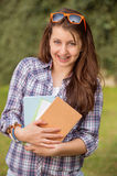 Happy student with braces holding books outside Royalty Free Stock Image