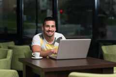 Happy Student At Cafe Using Laptop. Young Male Student Drinking And Having Fun With Laptop In Cafeteria Stock Photos