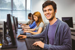 Happy student in computer class smiling at camera Royalty Free Stock Images