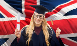 Happy student with diploma over british flag. Education, gesture and people concept - happy female student in mortar board and bachelor gown with diploma Royalty Free Stock Image