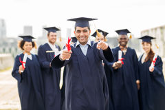 Happy student with diploma pointing finger at you Royalty Free Stock Images