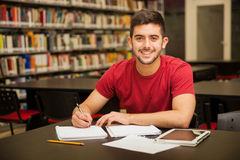 Happy student doing homework. Attractive male university student doing some homework in the school library and smiling royalty free stock image