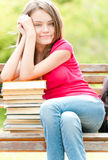 Happy student girl  on bench with pile of books. Beautiful and happy young student girl sitting on bench, her hands on pile of books, smiling and looking into Stock Photos