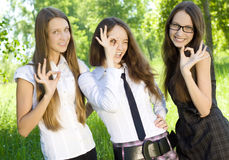 Happy student girl give the sign okey in the park. Three happy student girl give the sign okey in park Stock Photography