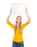 Happy student girl holding blank board over head Royalty Free Stock Image