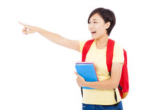 Happy student girl holding books and pointing Royalty Free Stock Image