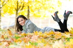 Happy student girl lying in autumn Royalty Free Stock Images