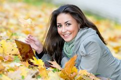 Happy student girl lying in autumn Royalty Free Stock Photos