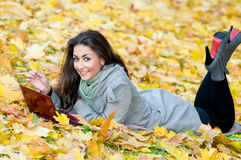 Happy student girl lying in autumn leaves Stock Photos