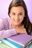 Happy student girl purple pile of books Royalty Free Stock Images