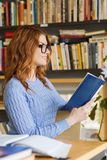 Happy student girl reading book in library Stock Photos
