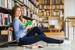 Happy student girl reading book in library Stock Photo