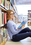 Happy student girl reading book in library Royalty Free Stock Image