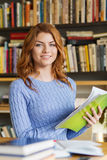 Happy student girl reading books in library Stock Image