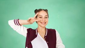 Happy student girl showing peace sign over green. People, school, education and gesture concept - happy smiling pretty teenage student girl showing peace sign stock image