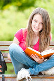 Happy student girl sitting on bench with book. Beautiful and happy young student girl sitting on bench, holding book in her hands, smiling and looking into the Royalty Free Stock Image