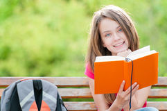 Happy student girl sitting on bench with book. Beautiful and happy young student girl sitting on bench, holding book in her hands, smiling and looking into the Royalty Free Stock Photography