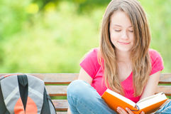 Happy student girl sitting on bench with book. Beautiful and happy young student girl sitting on bench, smiling and reading book. Summer or spring green park in Stock Image