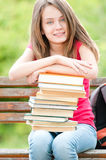 Happy student girl sitting on bench and smiling. Beautiful and happy young student girl sitting on bench, her hands on pile of books, looking into the camera and Royalty Free Stock Images