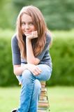 Happy student girl sitting on books Royalty Free Stock Images