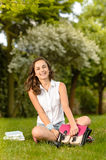 Happy student girl sitting grass open schoolbag Royalty Free Stock Image