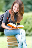 Happy student girl sitting on pile of books Stock Image