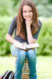 Happy student girl sitting on pile of books Royalty Free Stock Photography