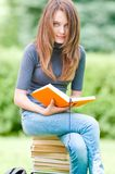 Happy student girl sitting on pile of books Stock Photos