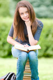Happy student girl sitting on pile of books Royalty Free Stock Image