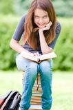 Happy student girl sitting on pile of books Stock Photo
