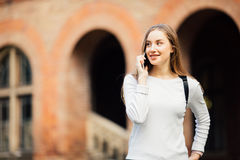 Happy student girl speaking mobile outdoors near University. Happy student girl speaking mobile outdoors spring Royalty Free Stock Images