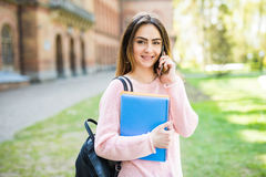 Happy student girl speaking mobile outdoors summer campus exam time. Happy student girl speaking mobile outdoors spring Stock Photos