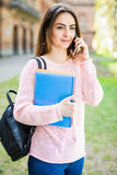 Happy student girl speaking mobile outdoors summer campus exam time. Happy student girl speaking mobile outdoors spring Stock Images