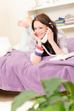 Happy student girl speaking on phone lying Royalty Free Stock Photography