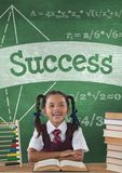 Happy student girl at table against green blackboard with success text and education and school icon Royalty Free Stock Photos