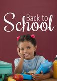 Happy student girl at table against red blackboard with back to school text Stock Images