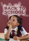 Happy student girl at table against red blackboard with back to school text. Digital composite of Happy student girl at table against red blackboard with back to Stock Photo