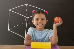 Happy student girl at table holding an apple against grey blackboard with school and education graph. Digital composite of Happy student girl at table holding an Royalty Free Stock Photography
