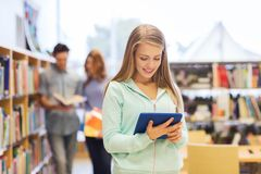 Happy student girl with tablet pc in library Royalty Free Stock Photos