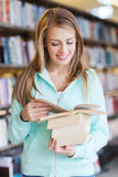 Happy student girl or woman with book in library Stock Images