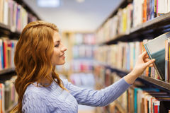Happy student girl or woman with book in library. People, knowledge, education and school concept - happy student girl or young woman taking book from shelf in Royalty Free Stock Photos