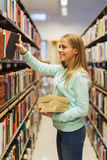 Happy student girl or woman with book in library Stock Image
