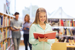 Happy student girl or woman with book in library Royalty Free Stock Photography