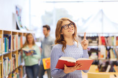 Happy student girl or woman with book in library Stock Photo